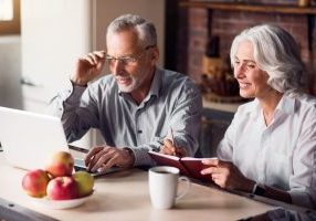 Working mood. Senior couple sitting at the kitchen table looking at something on a laptop and smiling