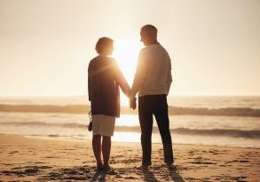 Rear view of a senior couple holding hands on the beach. Mature couple standing together on a seashore at sunset.